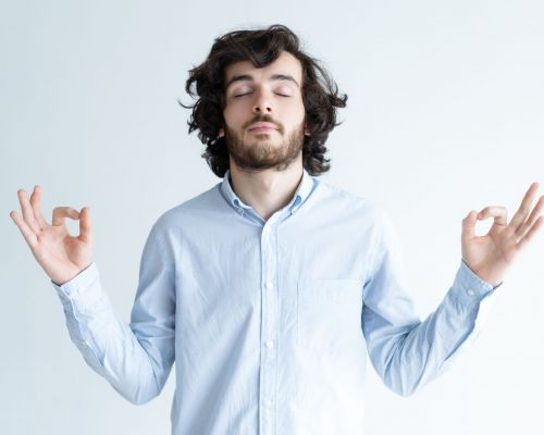 Peaceful young man meditating with his eyes closed and keeping hands in mudra gesture. Handsome guy concentrating. Harmony concept. Isolated front view on white background.