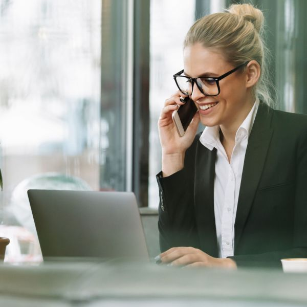 Photo of young happy smiling blonde business woman sitting indoors in cafe using laptop computer talking by mobile phone. Looking aside.