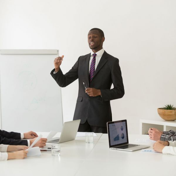 Confident african speaker business coach in suit giving presentation training sales team in office, black businessman speaking at seminar teaching people group presenting new marketing project goals