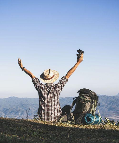 Tourist  from mountain top. sun rays. man wear big backpack against sun light