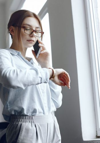 Girl is standing by the window.Woman talking on the phone.Brunette looks at her watch